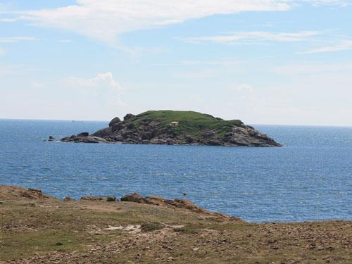 Sogar von den Sanddünen aus ist in weiter Entfernung diese vorgelagerte Insel zu erkennen. Mit ihrer üppig grünen Vegetation erinnert sie ein wenig an Irland. (Foto: spe)
