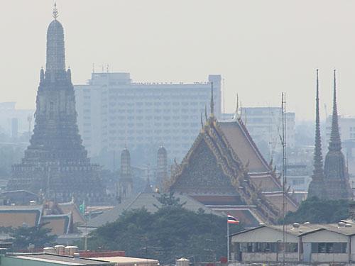 Bild mit Symbolcharakter: Der Blick vom Golden Mount (Wat Saket) über die dunstige Stadt hinweg auf den Wat Arun, dt.: Tempel der Morgenröte. (Foto: spe)