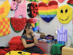 Bunter ist dieser Stand mit bunten (Kunst-)Blumengestecken - auch wenn die Verkäuferin erstmal mit Telefonieren beschäftigt ist. (Foto: spe)