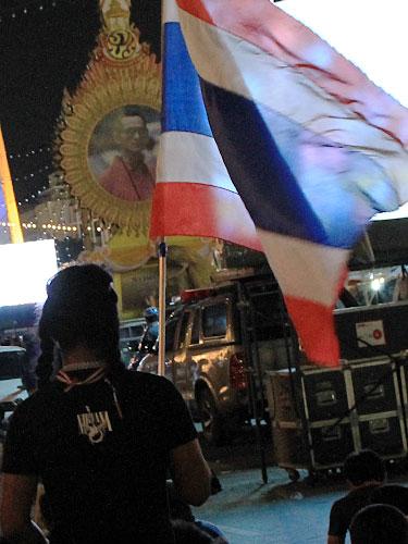 Ein Demonstrant schwenkt am Demokratiedenkmal die Nationalflagge Thailands. Im Hintergrund ein Bildnis von König Bhumibol. (Foto: Sören Peters)