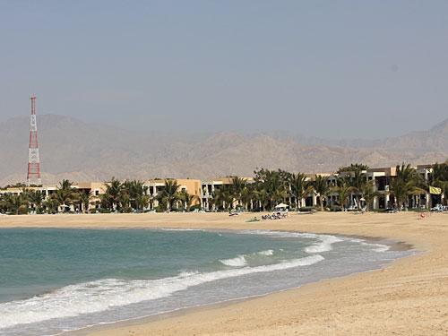 Die meisten Besucher kommen jedoch wegen des guten Wetters und wollen einfach nur entspannen, etwa hier am Strand des Hilton Beach Resort. Im Hintergrund sind die Ausläufer des Hadschar-Gebirges zu sehen. (Foto: Sören Peters)