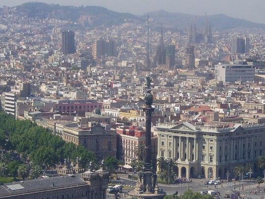 Blick aus der Hafenseilbahn über Barcelona. Vorne: Der Kreisverkehr mit der Kolumbus-Statue, links die Ausläufer der Ramblas. Hinten zu sehen: die Kathedrale La Seu und die Sagrada Familia. (Handyfoto: Sören Peters)