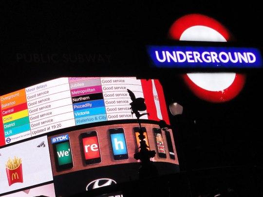 Tube-Schild am Piccadilly Circus. Im Hintergrund werden eventuelle Verspätungen angezeigt. (Foto: Sören Peters)