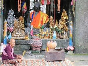 Eine ältere Frau bittet um Almosen vor einer Buddhastatue in einem Tempel nahe Angkor Wat. (Foto: Sören Peters)