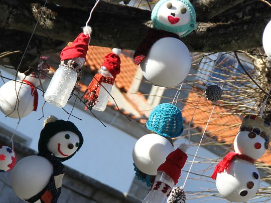 Kleine Schneemänner und -frauen in einem Baum. (Foto: Sören Peters)