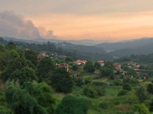 Schaurig und schön zugleich: Kleines Dorf bei Sever do Vouga im Sonnenuntergang. Im Hintergrund lodert ein Waldbrand. (Foto: Sören Peters)